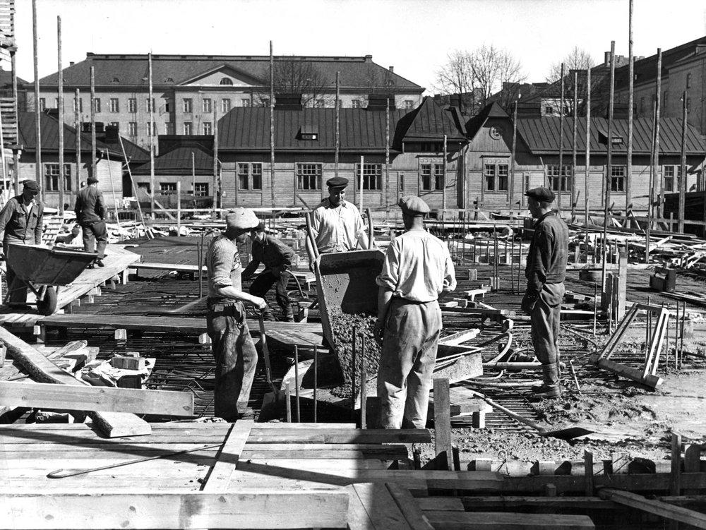 """Pauli Salomaan suunnittelema opiskelija-asuntola Domus Academica eli Domma rakennettiin vuonna 1947 lievittämään opiskelijoiden kasvavaa asuntopulaa. """"Domuksen boksi"""" olikin pitkään opiskelija-asunnon arkkityyppi. Kuvassa Domman työmaa Leppäsuolla vuonna 1946.  Kuva: HYYn arkisto (1946)"""