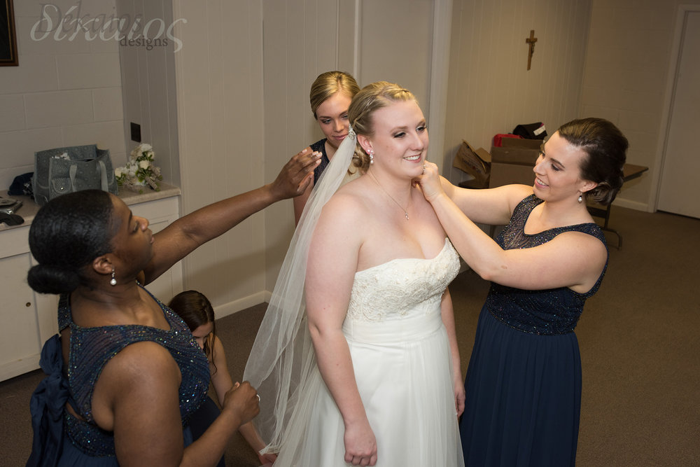 Her bridesmaids helping with the finishing touches. (Okay, this is staged, but how fun!)