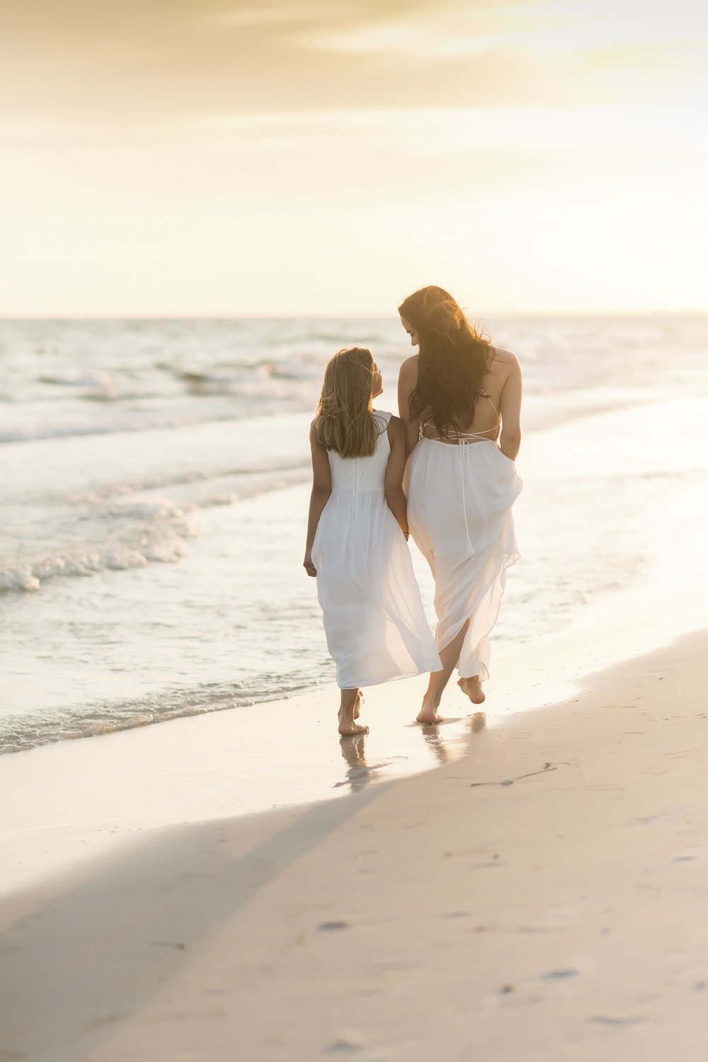 Vacationing mother and daughter walk during beach session