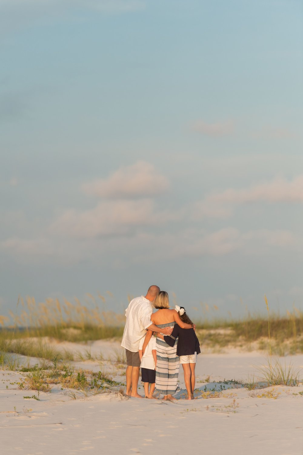 beach photo session of hugging family at sunset