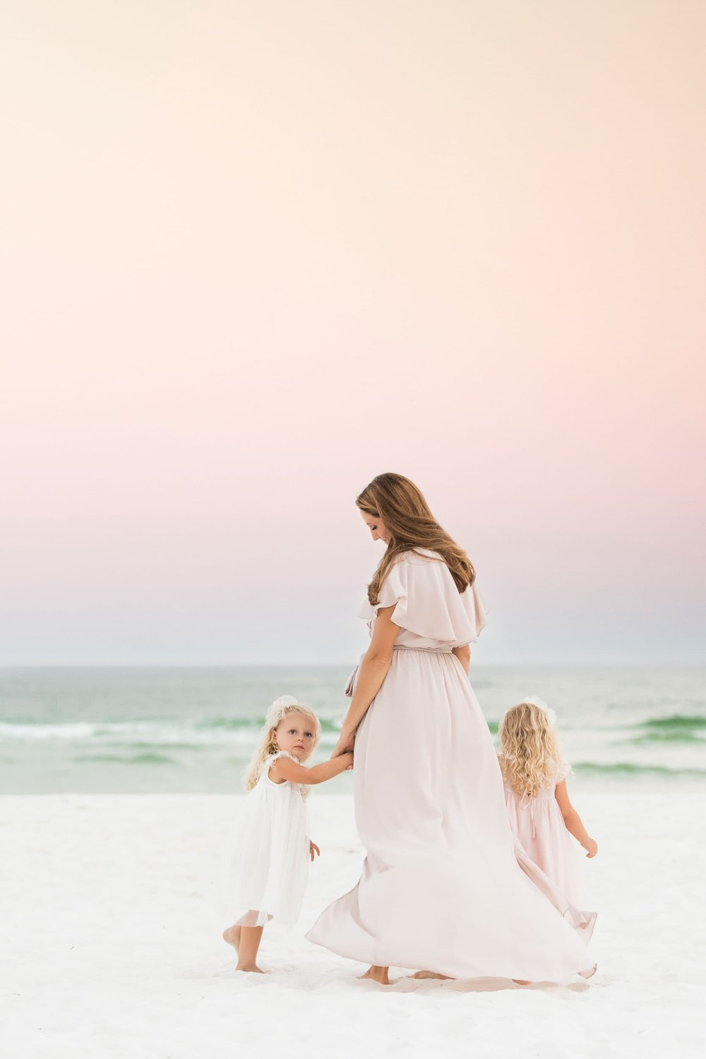 pensacola beach photographer takes sunset portrait of mother and girls at the beach