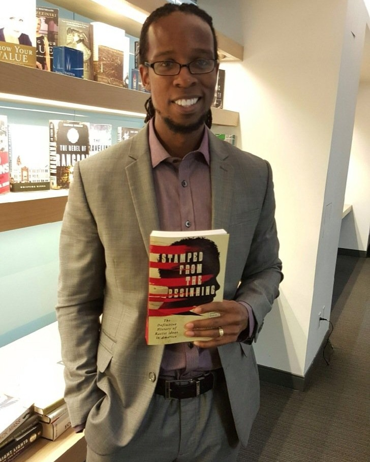 "Dr. Ibram X. Kendi holds a copy of his published work,  ""Stamped From the Beginning"" ."
