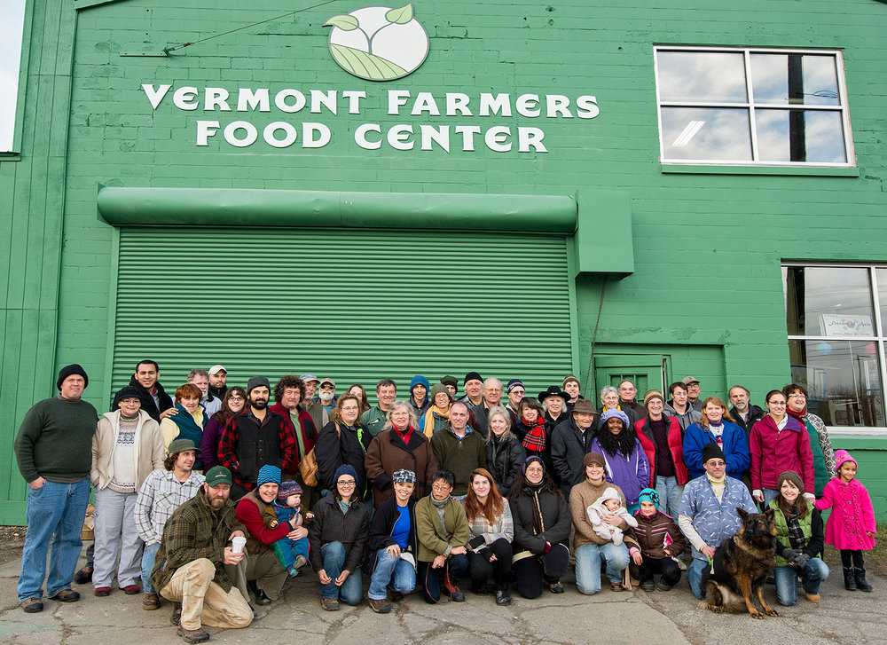 Vermont Farmers Food Center volunteers stand in front of NEGRF signage by William Jalbert, photographer.