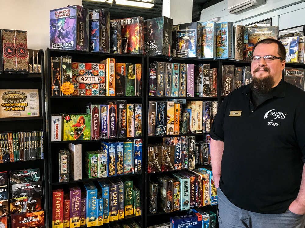 Tony Vandenberg, owner of Black Moon Games in Rutland, VT stands in front of popular tabletop games at his store.