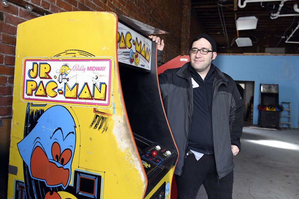 """""""Nick Grandchamp poses next to his Jr. Pac-Man machine Tuesday morning at a pop-up arcade gallery set to open this weekend."""" Photo courtesy of  Robert Layman  / Rutland Herald Staff Photographer"""