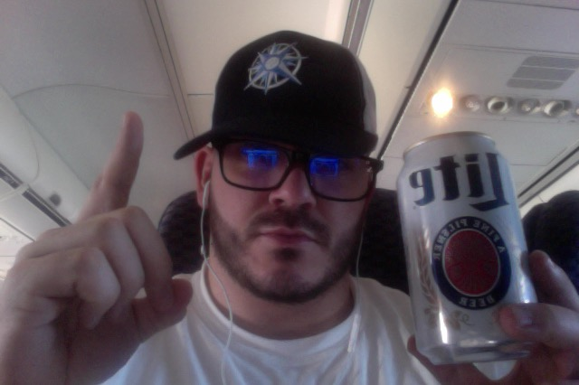 Mr. Manifest on an airplane starting his vacation the right way with a 7:30AM Road/Sky Soda