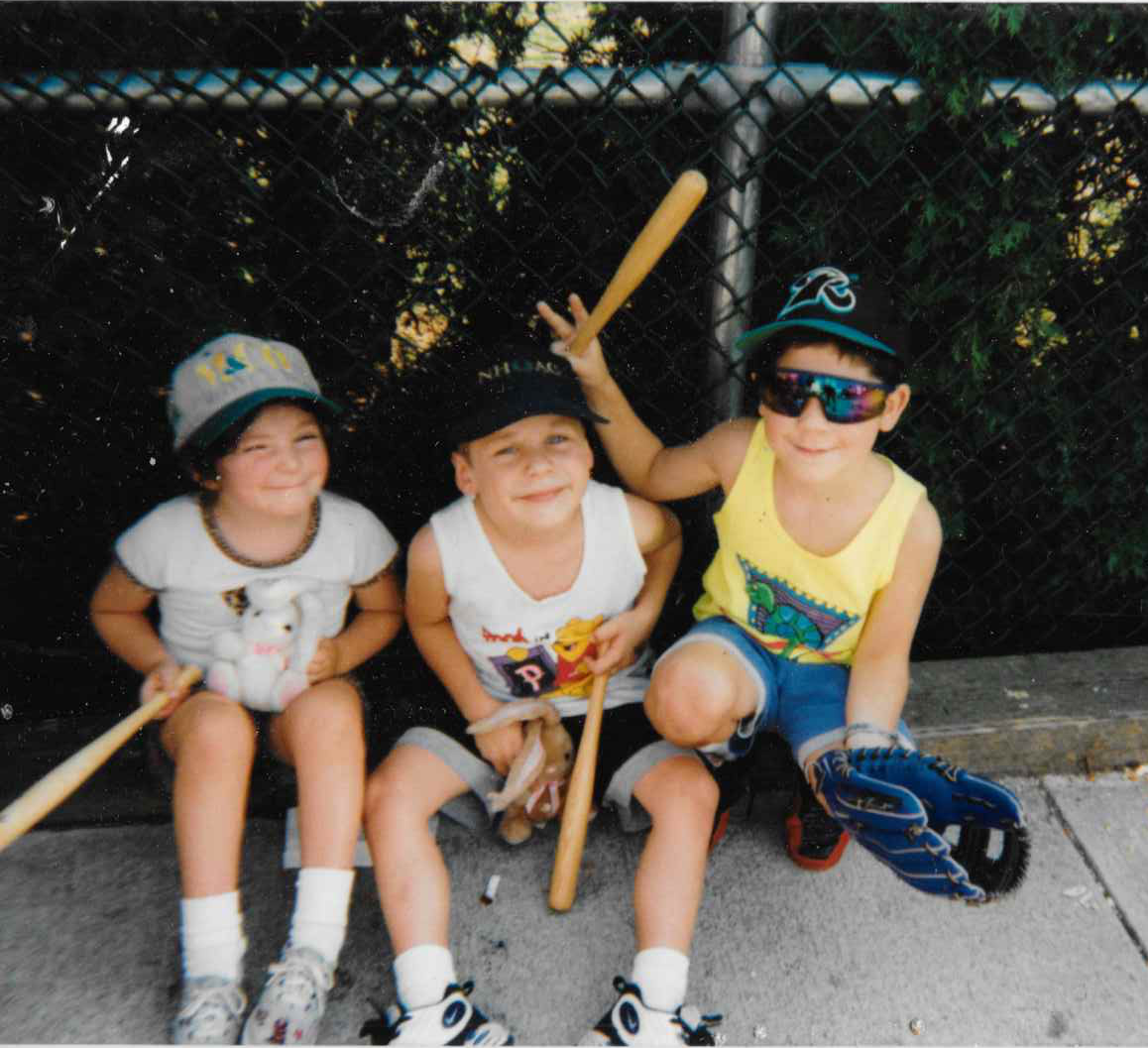 picture of three young children at baseball game, holding souvenir bats and one is giving ears to cousin