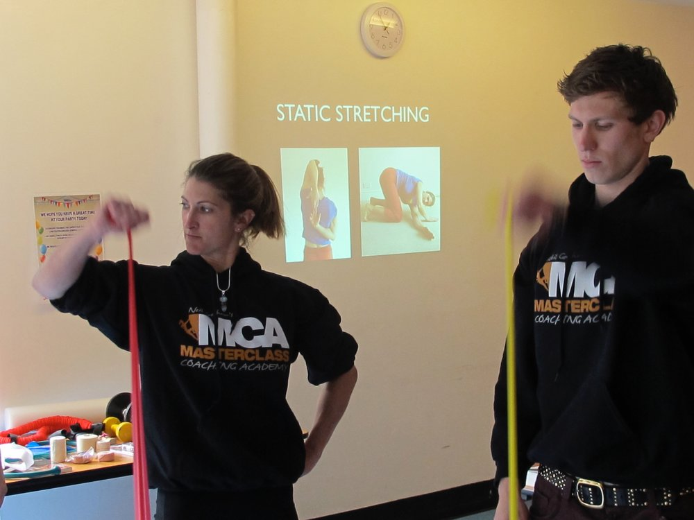 Nina Tappin demonstrating shoulder rehab exercises at an injury prevention seminar.