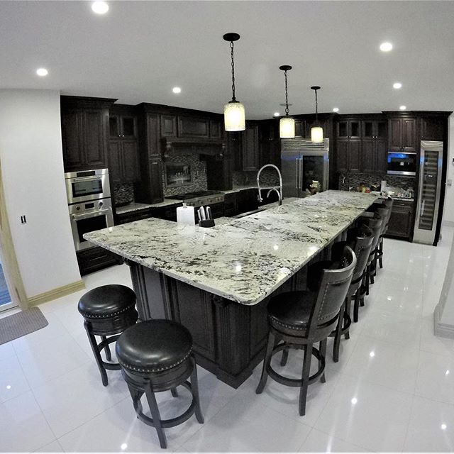 """The kitchen is the center of daily life and in most homes. Design and function are more important than ever when it comes to a kitchens layout. This West Islip waterfront homes kitchen was perfectly designed for entertaining friends and family.  Gorgeous white porcelain floors, led lighting, large """"L"""" shaped bi-level island area with plenty of guest friendly seating, Stone accent wall, glass tile mosaic backsplash with """"last supper"""" mural inlay, wolf 6 burner commercial stove, pot filler for added convenience when cooking, large capacity wine fridge, convenient wall cabinet coffee station, double wall oven, solid surface countertops, bar sink, and stunning waterfront views provide the perfect compliment to this wonderfully designed kitchen area. Call Cascella & Sons @ 631-582-0100 for your next total kitchen renovation! . . . #luxurykitchendesign #luxurykitchen #kitchen #kitchenremodel #kitchenrenovation #kitchensofinstagram #kitchencabinets #potfiller #farmsink #waterfronthomes #kitchenisland #lastsupper #kitchendecor #tilework #whitefloor #stoneaccentwall #westislip #wolfappliances"""