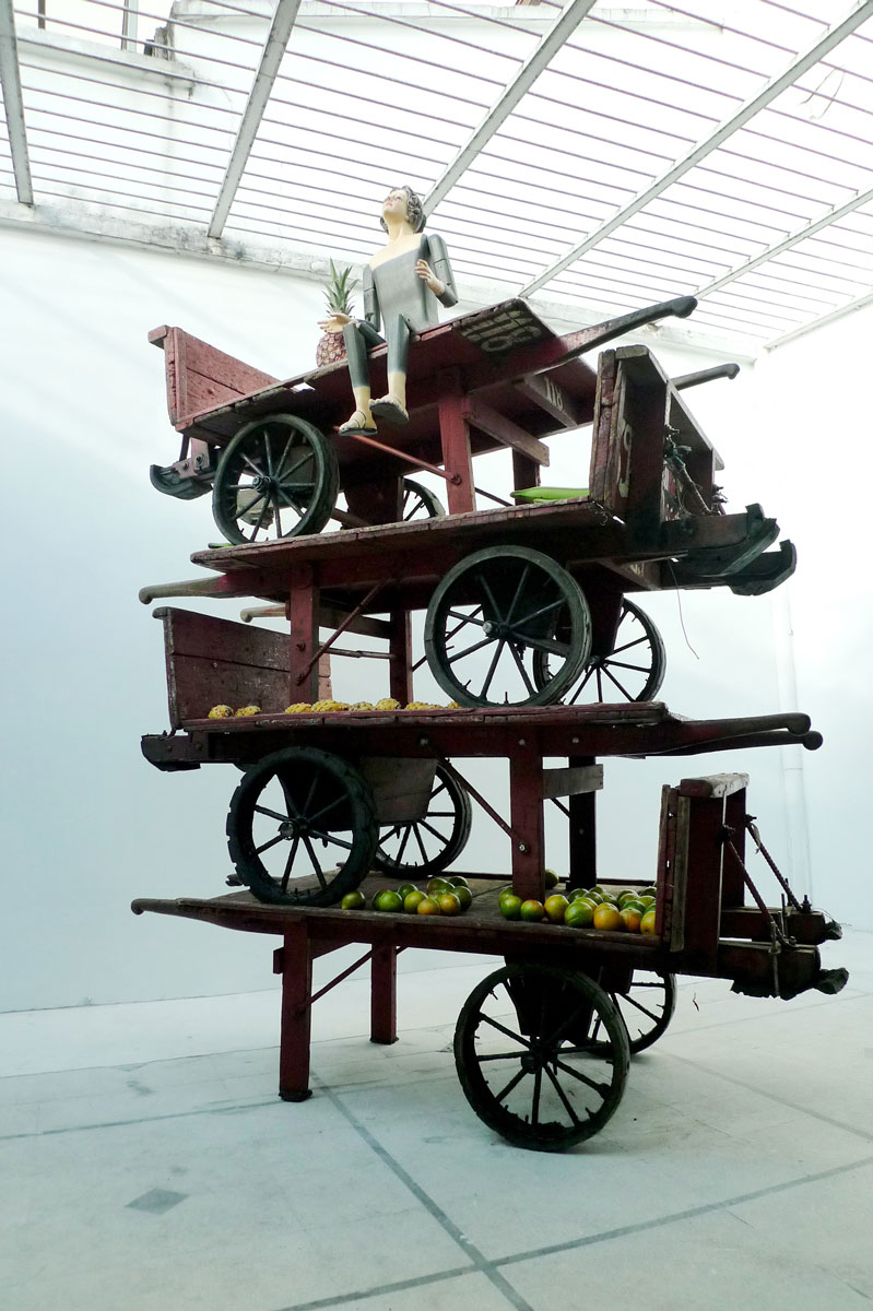 The Virgin Mary of Medellin , 2011 wooden carts, painted wood mannequin, and fruit 103.5 x 83.5 x 36""