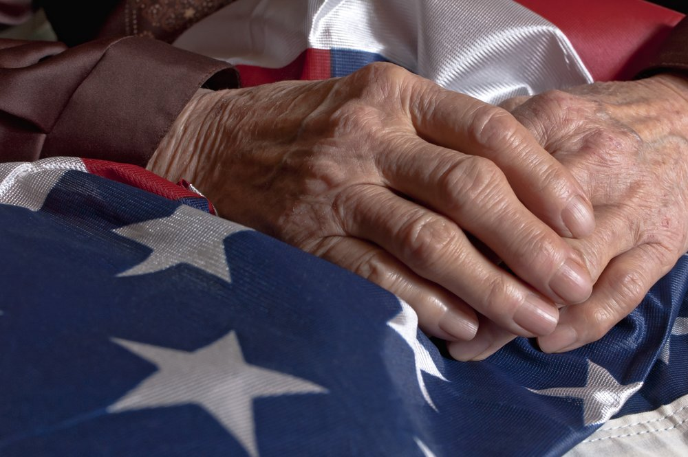 Time worn hands folded on American flag.jpg