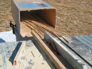 To catch these long ties as they come off the saw I place a stereo speaker box on saw horses. The ties slide into the box with each pass through the saw. Strips with knots will break apart yielding shorter strips. No problem. They'll all work.