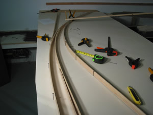 Begin by laying out approximate track locations with the splines. I usually start with the mainline, then to passing sidings, then to spurs. Flathead common nails are driven into the homasote or micore subroadbed far enough to hold the spline in position. Spring clamps hold the splines together where turnouts ocurr. I generally don't worry about what the turnout frog number is, as long as it's appropriate for the location. Frog numbers are essentially undefined- being, for example a #9.27 when measured after completion. And using this method produces a lot of flowing, curved turnouts- and trackwork in general. If a turnout with a true, straight route is desired, clamp a 2' level to the spline along the straight route and then arc a diverging route/spline from it.  Here is where things get interesting as scenery and structure locations transition from paper and pencil drawings to 3-D. And this is where a lot of rethinking takes place. Many nails get pulled, splines shifted, and ......hmmmm, maybe it needs to go like this...