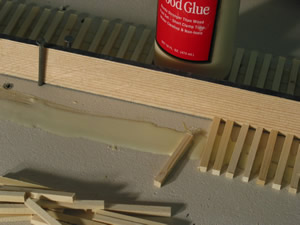 "I use Titebond yellow glue. I'll run a bead of glue about 18"" and spread with a stick, intentionally leaving a gap on the spline-side. One end of the tie is placed in the glue and then slid through the glue and up against the spline. This keeps the minimum amount of glue from getting on the spline.  If you've cut your own ties as described on the ""Cutting Ties"" section, there will be some ties with knots material in them. Toss those aside as they will not sand evenly later on.  The distance between ties, and their alignment can be varied depending on whether the track is main line, siding, or little used industrial."