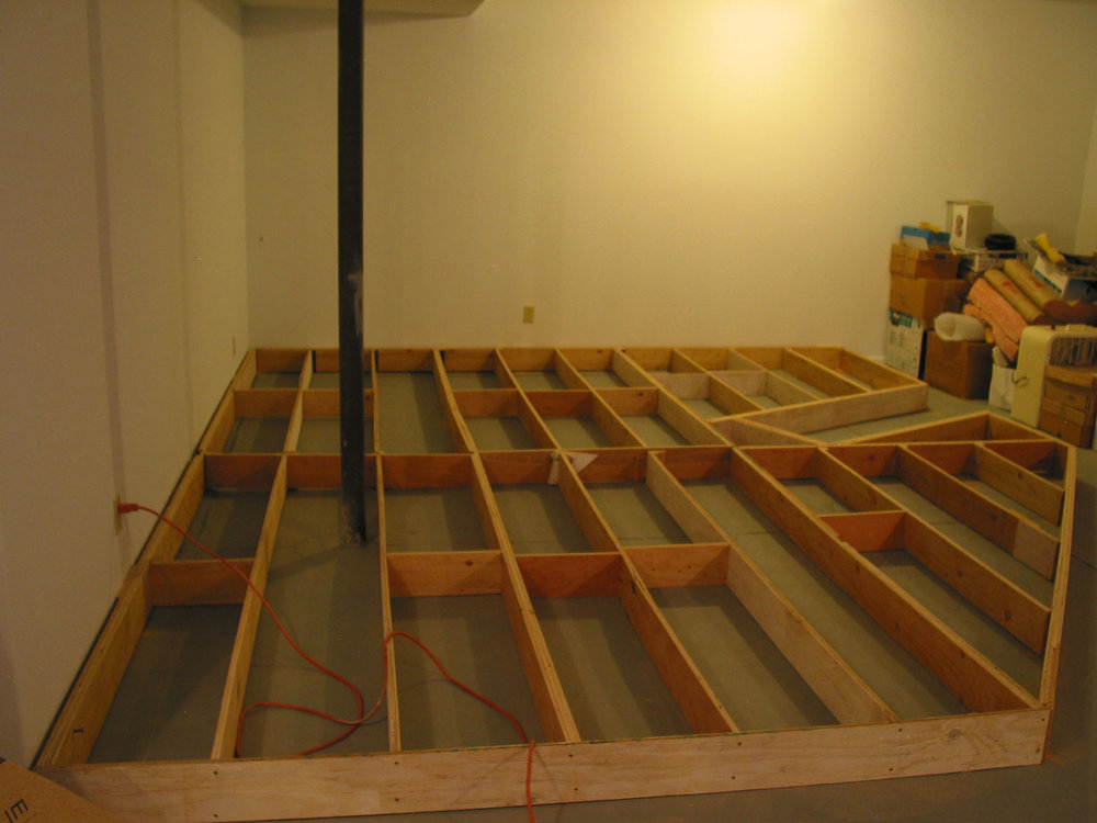 "The mailnline here reaches 61"", so a raised floor is necessary to keep operations at a reasonable height. A 6"" high framework of ripped plywood was anchored to the walls and glued to the floor."