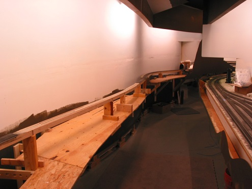 Plywood forms the future riverbed under a pin-connected truss and more distant, plate girder bridge. Lighting and valance have been added. Morrison is on the right of the aisle.