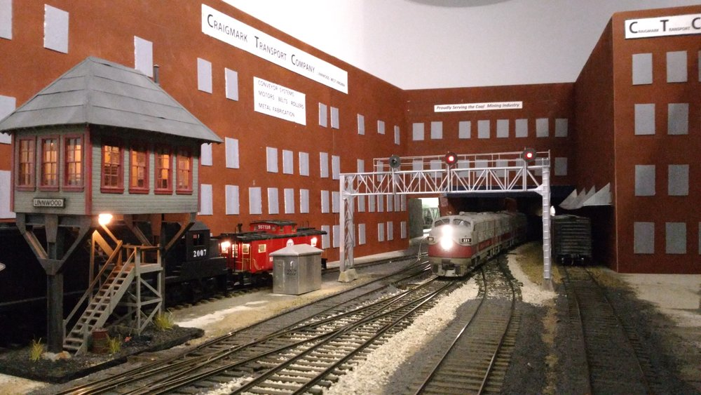 Finally. The train enters Linnwood, passing under a mock-up of Craigmark Transport Corp. (CTC   :) This is the town where it's always raining,...and lightening, thanks again to the ingenuity of Bob Sobol.