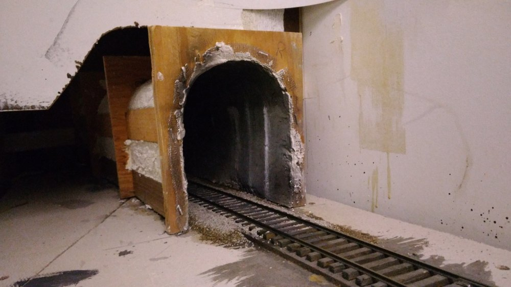 Leaving Apex we dive into Rockcut Tunnel. Lining the full length of a tunnel where possible makes sound equipped locos an awesome experience. The sound builds and the anticipation rises. The only thing missing is the hot blast.  Wood tunnel formers are cut on a band saw; thin strips of wood glued to the inside (sectioned for the top piece if on a curve); screen wire stapled on; drywall mud applied; hot glued in place. Be sure to ballast the track first. :( The portal is then attached and scenery blended. See next picture for the other end!