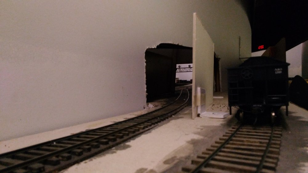 "While this view thru the future tunnel will be blocked once scenery is in place, at  the moment we can peep through into Linnwood Yard and see the signal bridge that gave us the ""green"" to begin our journey. Kayford is ""dark territory"" with traffic being managed by Track Warrant."