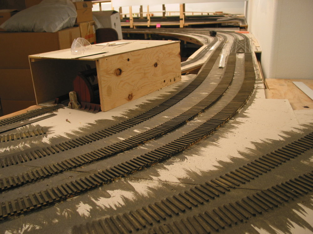 The ties are in place into Glen Forge. The Bayfield double-crossover can be seen in the distance  looking down the mains. A plywood cocoon encases the rotary to protect from damage during this phase of construction.