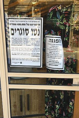 Posters in a shop window on Eilat Street in Tel Aviv's garment district, March 7, 2018. (Simona Weinglass/Times of Israel)