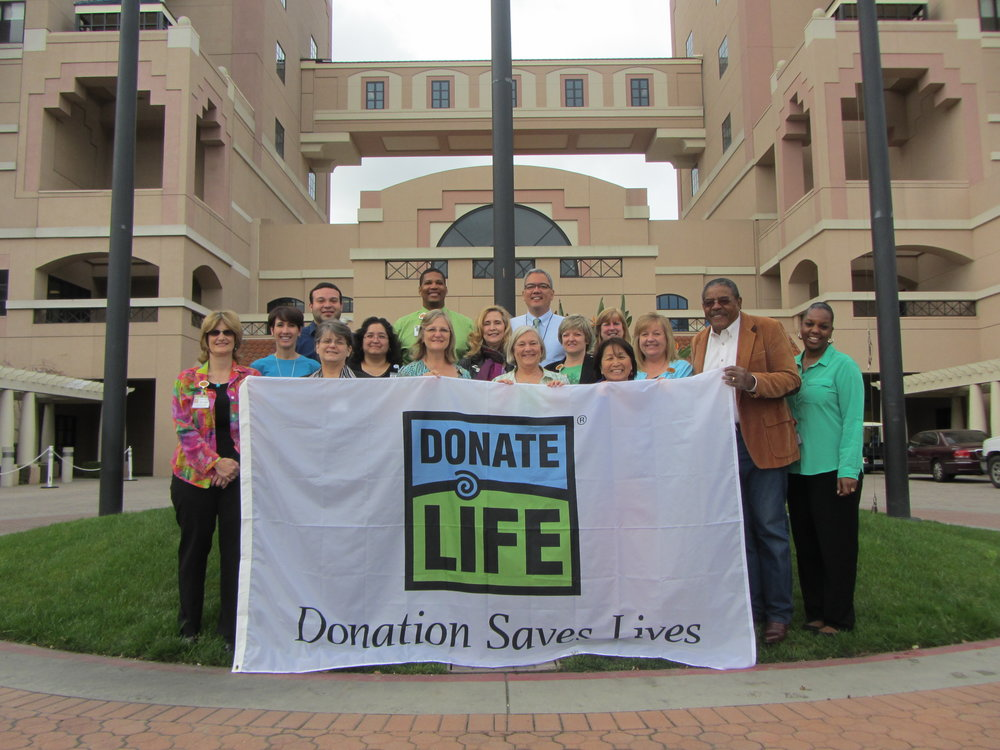 Hospital staff, donor families and recipients prepare to raise a Donate Life flag in front of Huntington Hospital in Pasadena, Calif.