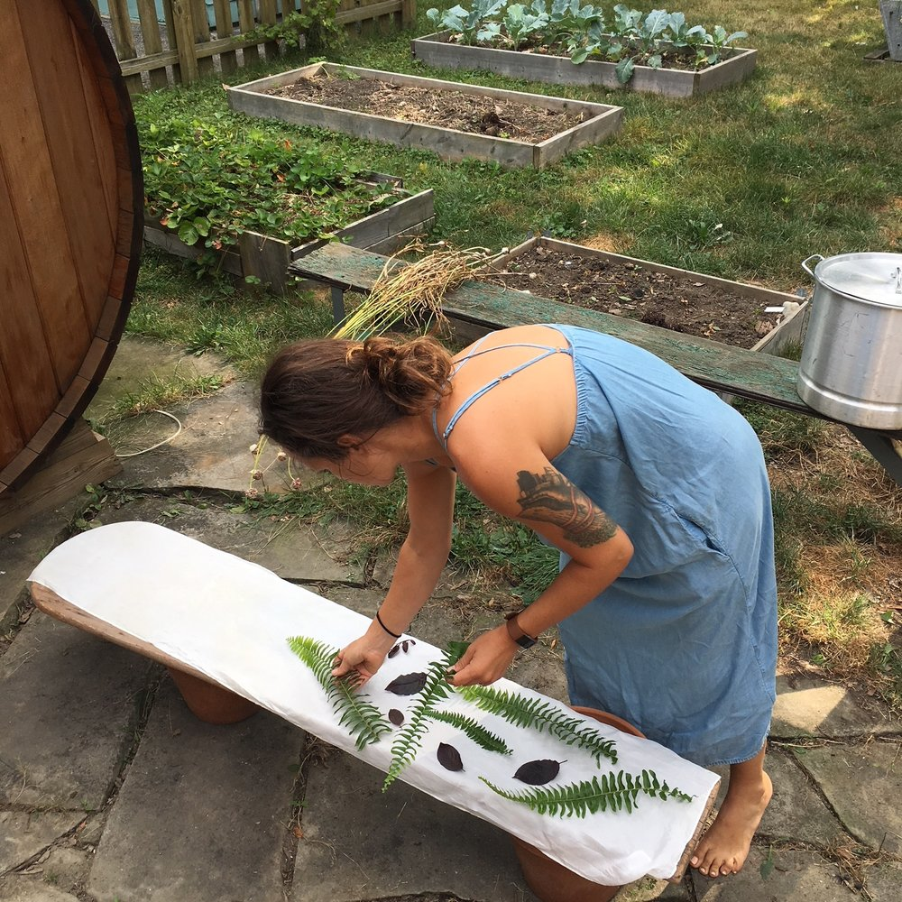 Jess, in her backyard,lays out the design for a raw silk table runner, eco-printed.