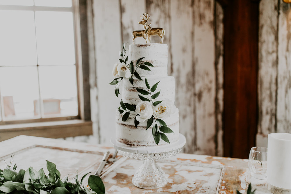 Elegant natural white wedding cake with white rose floral accents and unique golden deer wedding cake topper