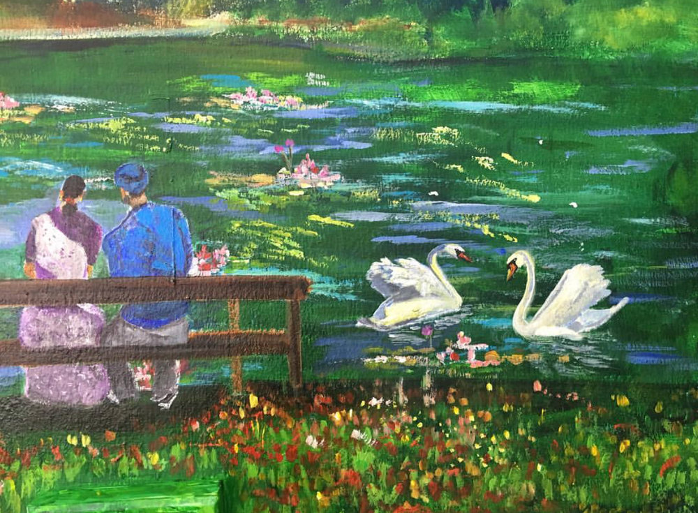 An Indian couple sitting by the pond where the swans are.  Singapore is diverse in its ethnicity and people from all races are featured here enjoying the space and nature that we have in this country.
