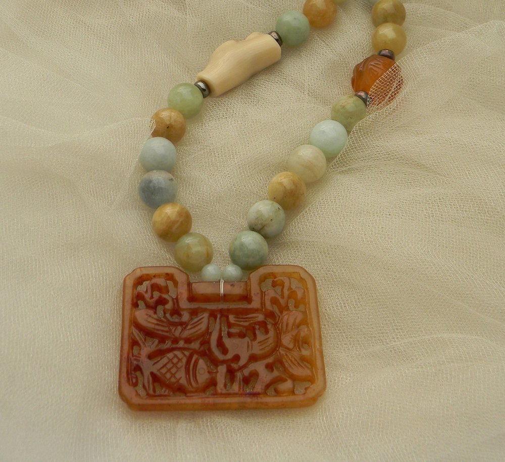 Carved carnelian lock pendant on aquamarine beads necklace ,
