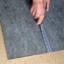 3. It is usually necessary to cut tiles at the perimeter of the room, unless they happen to fit perfectly. Using a basic utility blade and a straight edge, flip the tile over and begin a long, gentle cut. Repeat several times if needed, until the tile can easily fold. It is not necessary to try to cut all the way through to the yarn in one motion. Use care to avoid injury.