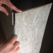 4. When the tile can fold easily along the cut line, stand it on end. Glide the utility blade down the fold in order to cut the yarn fiber.