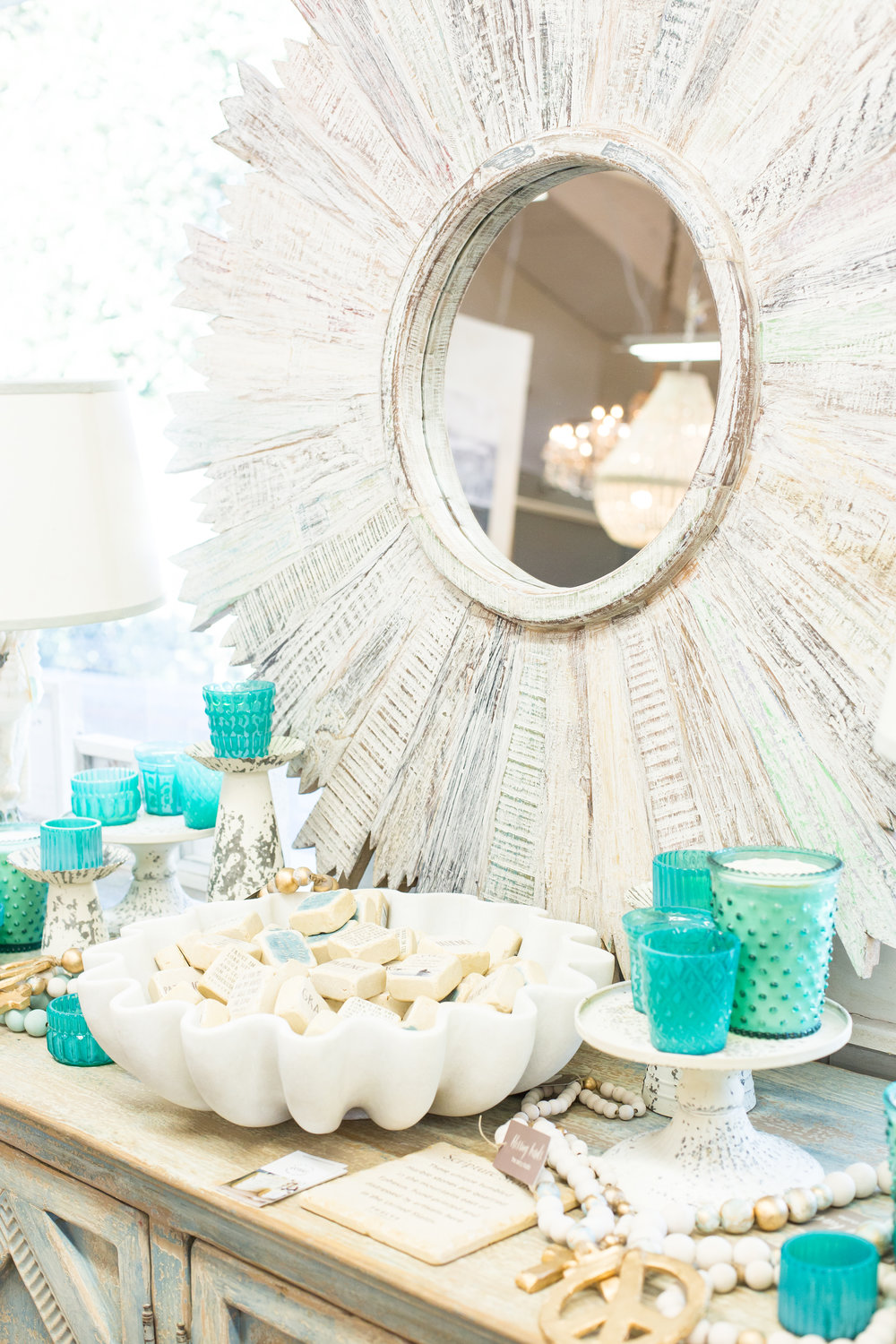 White sunburst mirror, candles, decor