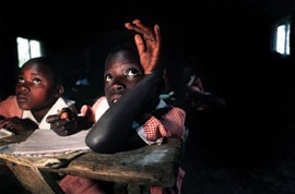 Risiki Auma Omollo, 7, (right) studies next to Elizabeth Akoth Okinyi, 8, in Edward Olango's class in the primary school. The students study in dark classrooms because the school is lacking many basic resources, such as electricity.