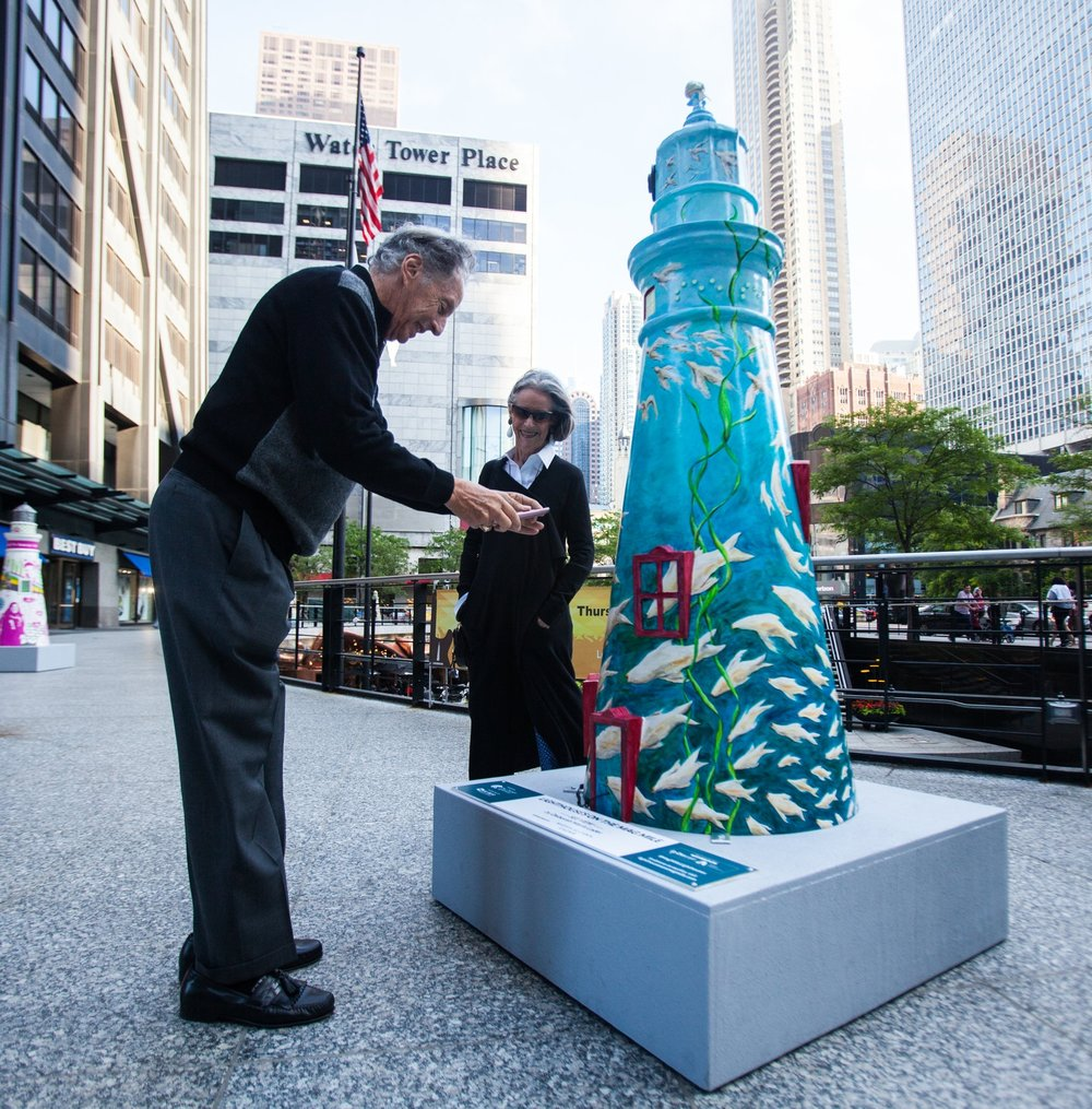 Onlookers snap a photo of one of the lighthouse sculptures now on The Mag Mile.