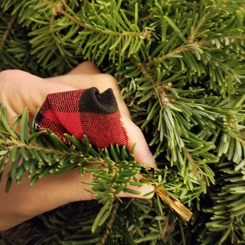 Step 2 - Select a location that you like on the wreath and secure the remaining end of the twist tie around the branch. Try to place it far enough in that you do not see the fastener.