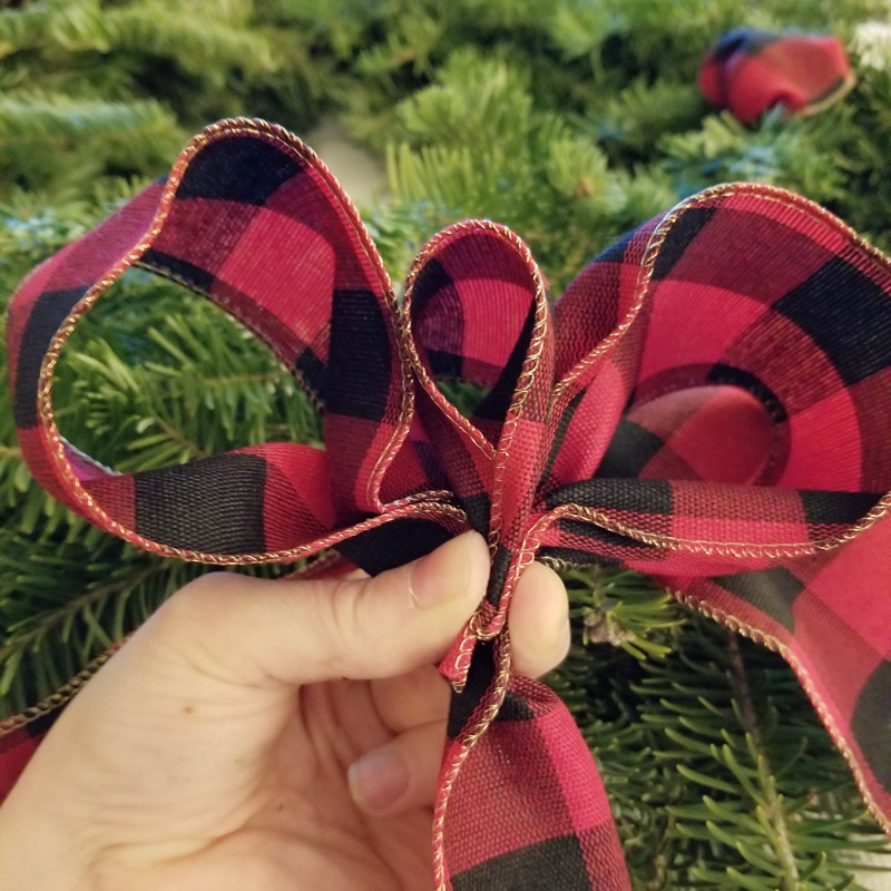 Step 9 - Make hills and valleys with your ribbon making sure to hold onto the bottom of each valley as you create how you want your bow to look. I decided I just wanted a simple, traditional bow. Since you have already secured the bottom of the bow to the wreath you do not need to allow any extra ribbon to hang down. Simply cut at the bottom of the last valley and secure with twist tie. {you may need a larger one for this because it gets thick. Also, be sure to twist it tightly}