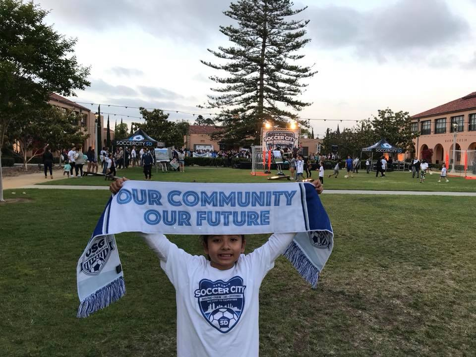 A young SoccerCity supporter hoists the scarf of the Original Supporters Group