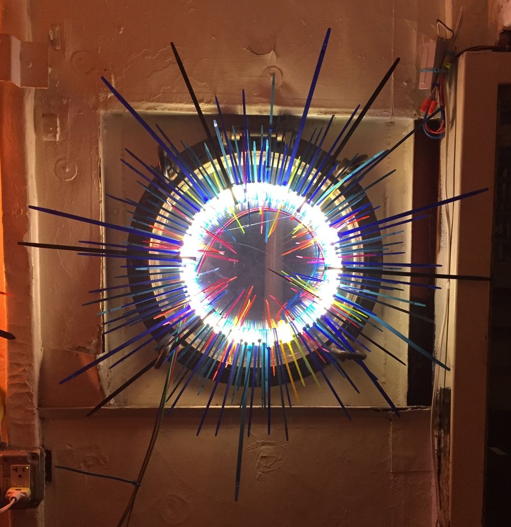 Untitled, Blue Quarters   Fluorescent Lamp, color snap ties, loom heddles and fishing spinners and color wire 12 in lamp diameter 24 in overall