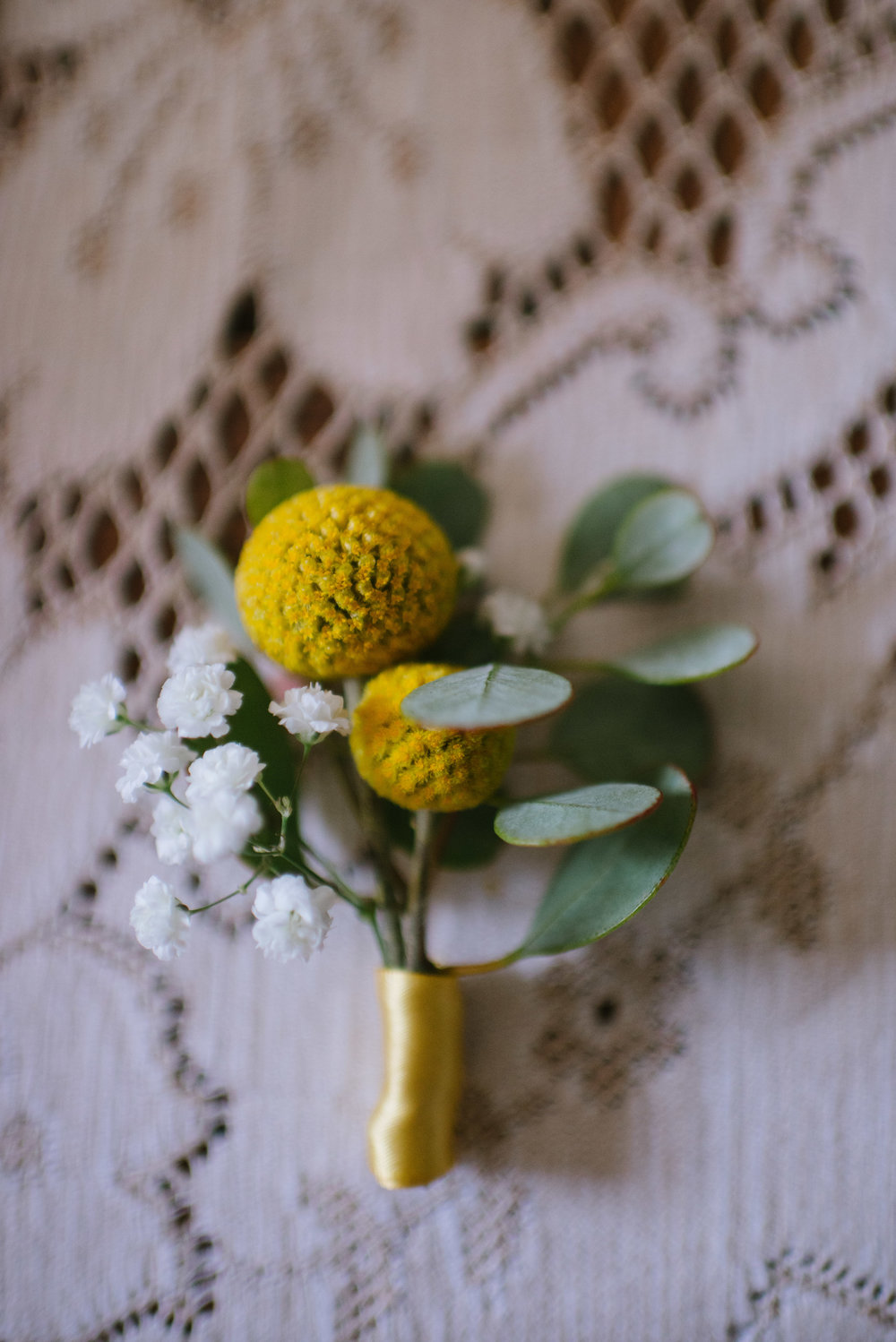 // boutonnières //   Stylish floral decorations, typically worn through the buttonhole (Fr: boutonniere) of a suit jacket or pinned to a lapel. Usually a single bud or small grouping of blooms worn by grooms, groomsmen, fathers and grandfathers, ushers, et al.