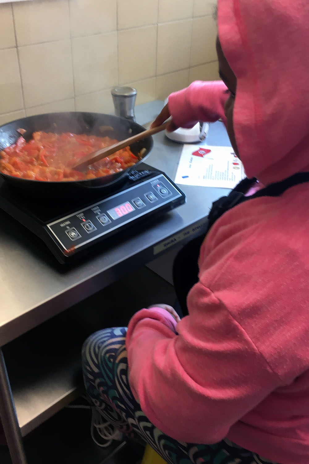 This student got a stool and practiced patience and care as the  shakshuka  cooked.