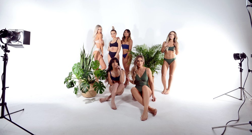 Tropical plants with models for a swimwear photoshoot.