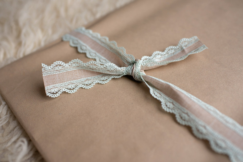a brown wrapped print with a lace trimmed bow tied on focus on the ribbon