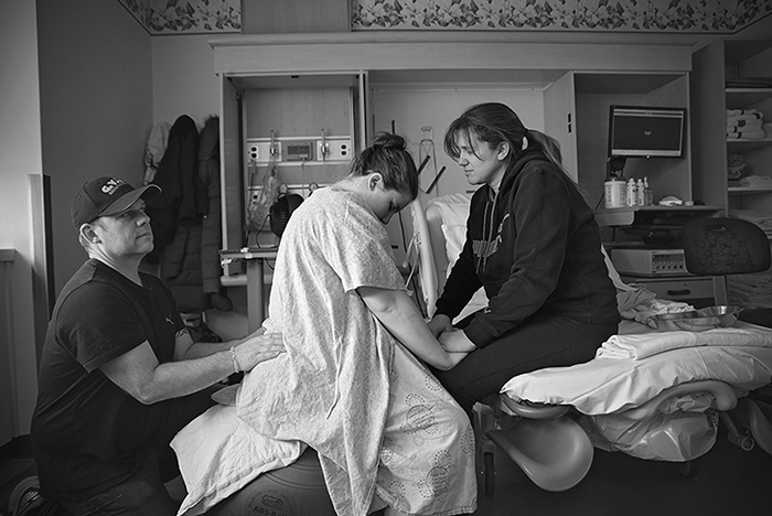 a labouring mother having support from her parents while in hospital sitting on a ball