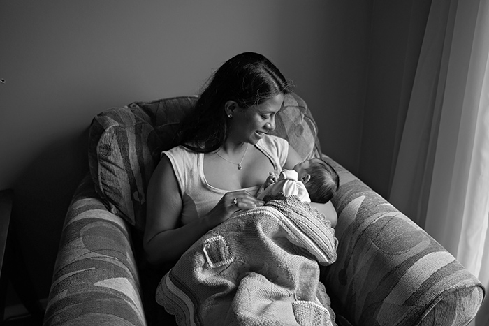 an ottawa mother sits on a chair at home lovingly gazing at her newborn baby wrapped in a knitted blanket