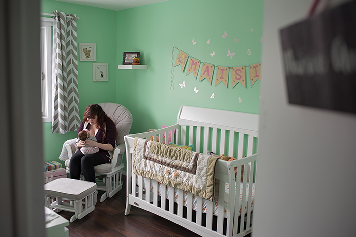 a mother sits on a rocking glider holding her newborn in the nursery of their ottawa home