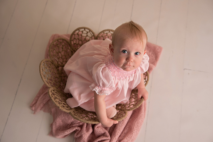 a baby girl sits in a basket wearing an old fashioned pink smocking dress looking up at camera