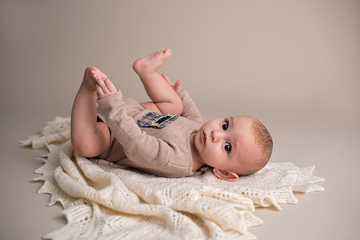 a baby lays on his back wearing a upcyled outfit on a knitted cream blanket in an ottawa photography studio