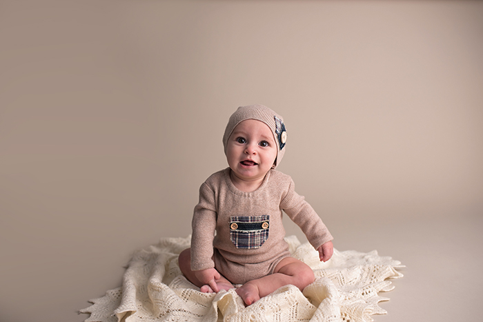 a baby sits on cream knit blanket wearing an upcycled outfit for sitter session in ottawa photography studio
