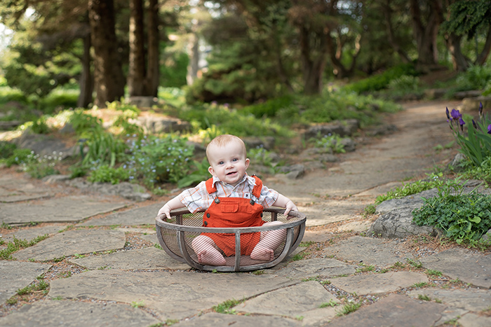 a baby sits in wood bowl at ottawa experimental farms garden wearing orange overalls for milestone sitter photography session